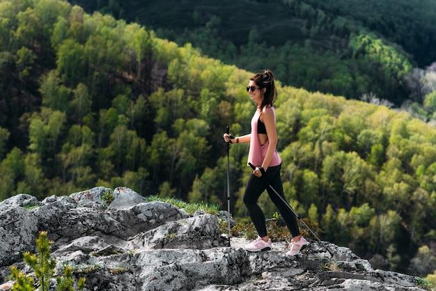 山でのハイキング。男は山の中をノルディックウォーキングに従事しています。山の観光客。若い女性が山の中をノルディックウォーキングをしていました。アクティブな余暇の時間の概念。コピースペース