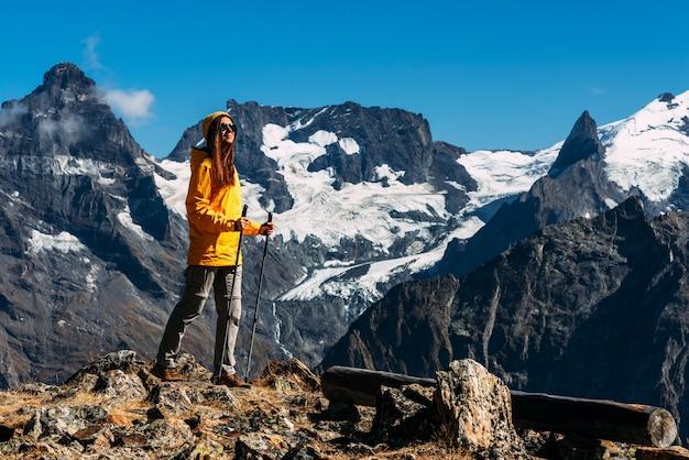 山でのハイキング。コーカサス山脈でノルディックウォーキングをしている人。山の頂上に向かう途中の女の子登山家。コーカサス山脈の観光客。コピースペース