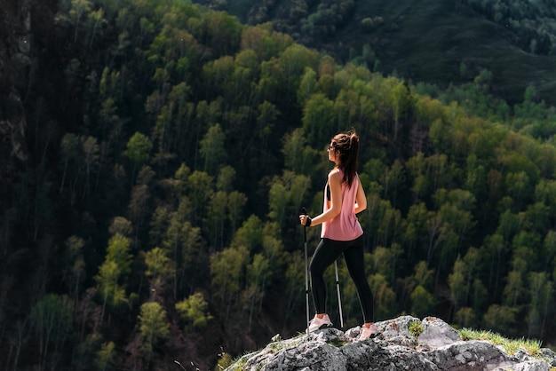 山でのハイキング。ノルディックウォーキングをしている女性。山の観光客。若い女性が山の中をノルディックウォーキングをしていました。アクティブな余暇の時間の概念。コピースペース