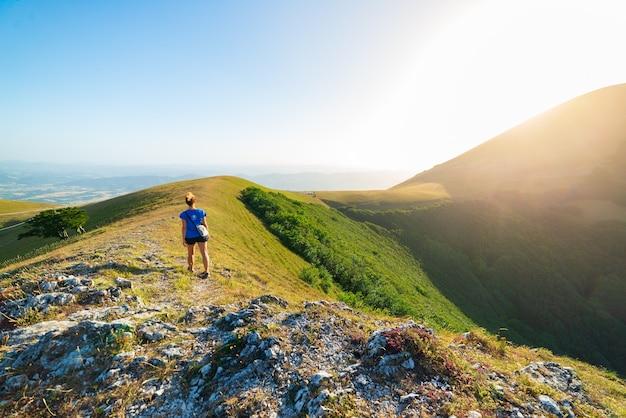 イタリア、アペニン山脈、モンテクッコのウンブリア地方の山々でのハイキング。緑の風景のユニークな丘や山の風景の中を歩く女性。夏の野外活動。