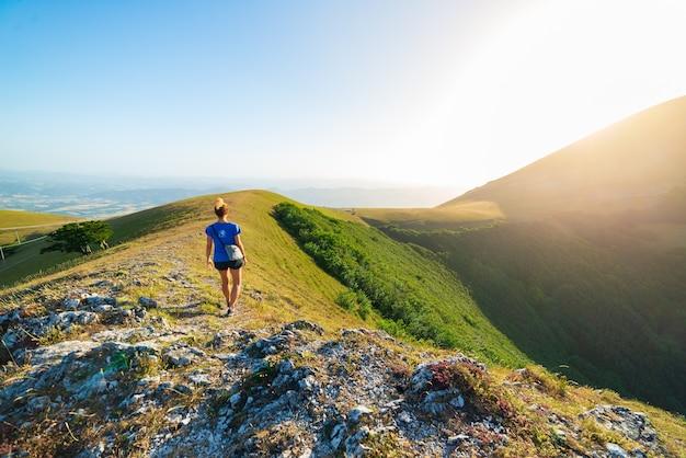 Поход в горы региона умбрия, монте-кукко, аппеннино, италия. женщина, идущая в зеленом пейзаже уникальных холмах и горном пейзаже. летние мероприятия на свежем воздухе.