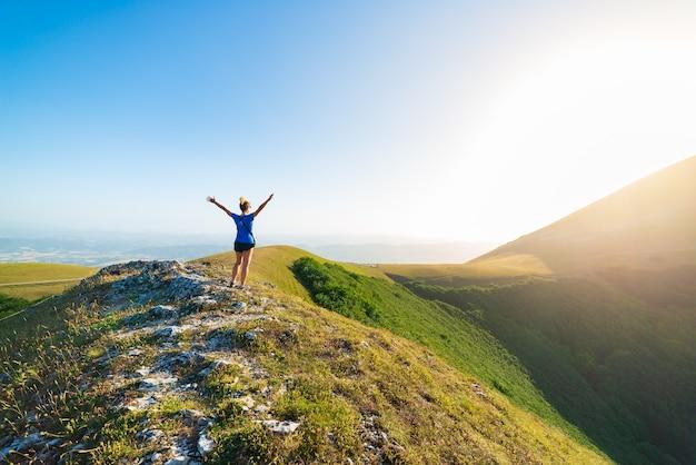 イタリア、アペニン山脈、モンテクッコのウンブリア地方の山々でのハイキング。緑の風景のユニークな丘や山の風景に腕を伸ばした女性。夏の野外活動。