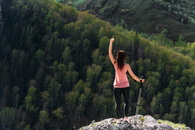 山でのハイキング。ノルディックウォーキングをしている女性、リアビュー。山の観光客。若い女性が山の中をノルディックウォーキングをしていました。アクティブな余暇の時間の概念。アスレチックガール。コピースペース