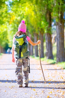 Hiking kid girl with walking stick and backpack rear view