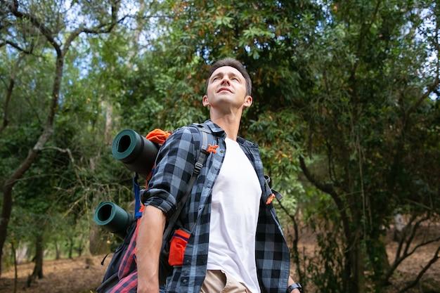 自然の風景を見ているハイキング男。景色を楽しみ、森の中を歩くバックパックを持つ魅力的な白人の若い観光客。観光、冒険、夏休みのコンセプトをバックパッキング