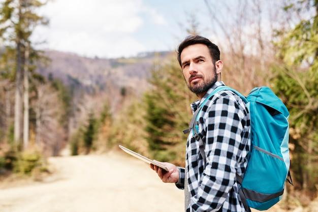 ビューで楽しんでいるバックパックとタブレットを持つハイキング男