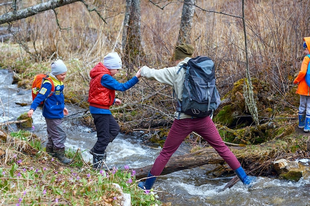 Hiking mother help children to cross mountain stream. sports family with backpacks