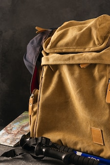 Hiking in the mountains concept. hipster backpack with map and walking poles