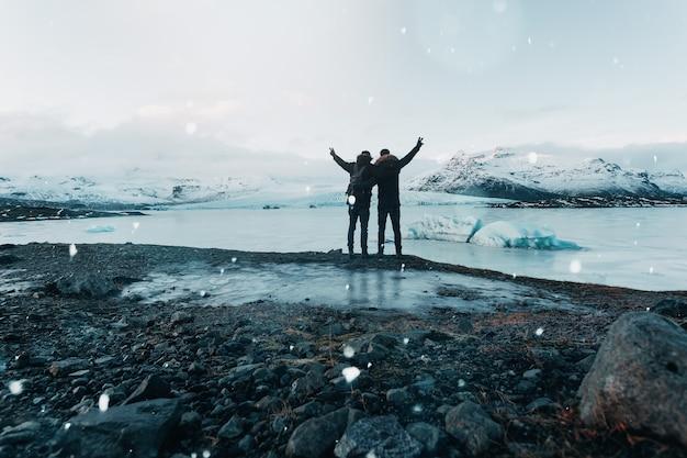 Поход по леднику в исландии, захватывающий вид, путешественник стоит на камне, которого достигли путешественники.