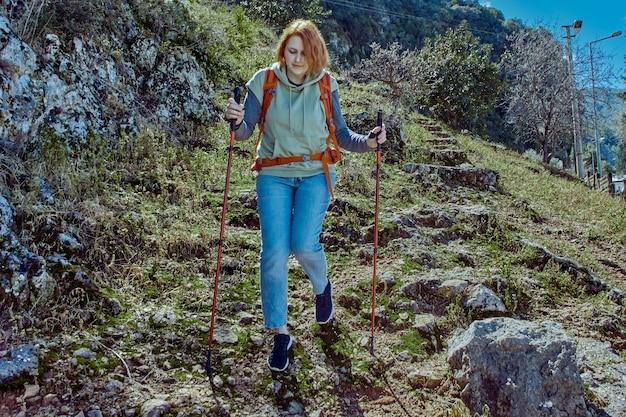 Походные палки помогают молодой женщине преодолевать высокогорье