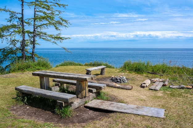Hiking resting place with benches, table, and campfire site next to lake baikal. blue sky with clouds and summer sun.