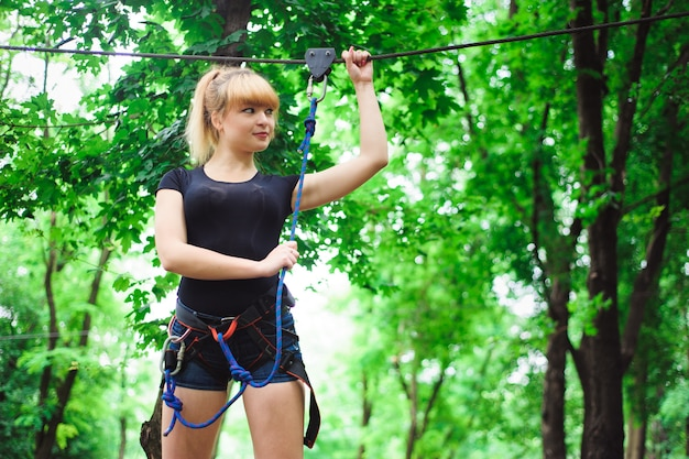 Hiking in the rope park young girl in the belt for insurance.
