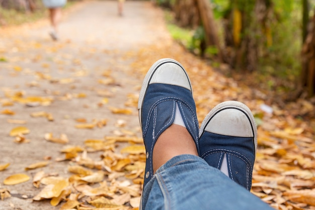 ハイキングシューズの若い女性の旅行者は夏の公園に座る。青いスニーカーの靴とジーンズの経路に焦点を当てる