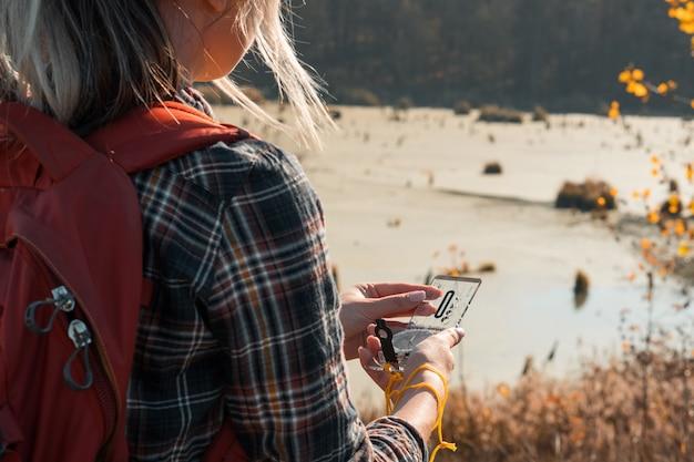 하이킹 관광 나침반을 사용하여 국가 늪과 가을 풍경을 탐험하는 숙녀의 자른 다시보기