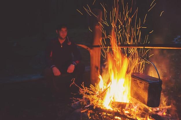 Ночью в лагере у костра отдыхает пеший турист. парень пьет чай у огня. мужчина смотрит на костер ночью.