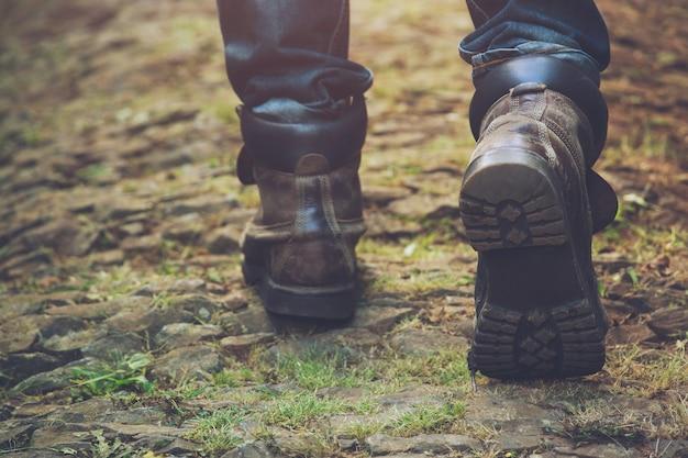 Походная тропа в действии в горах или лесу в походной обуви. мужские и женские туристические туфли. идут по лесной тропе в горных сапогах и с палками. место назначения