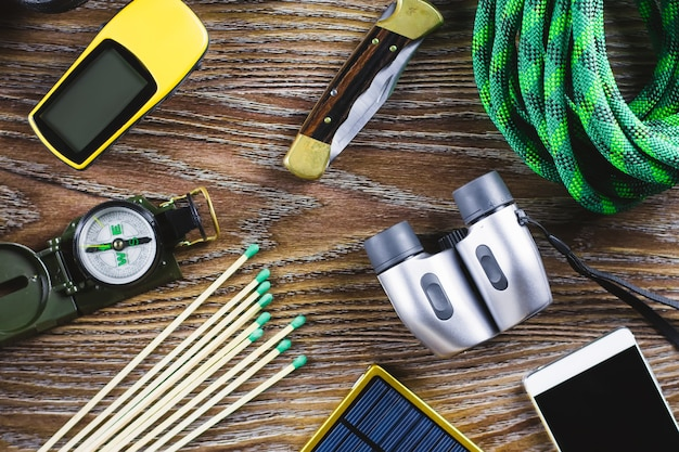 Hiking or travel equipment with boots, compass, binoculars, matches on wooden background