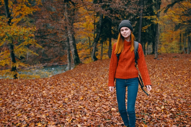 Hiking travel woman with backpack on her back and fallen dry leaves nature forest park model