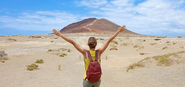 調達の腕で彼女の目標の達成を祝うハイキングの女性