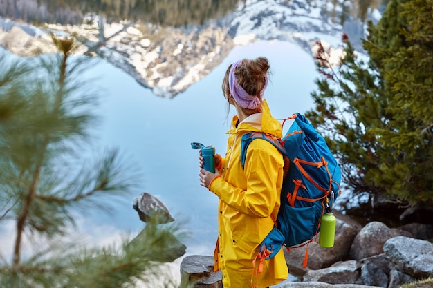 Hiking woman stops near lake in mountains, carries backback, holds thermos of hot beverage, explores something new