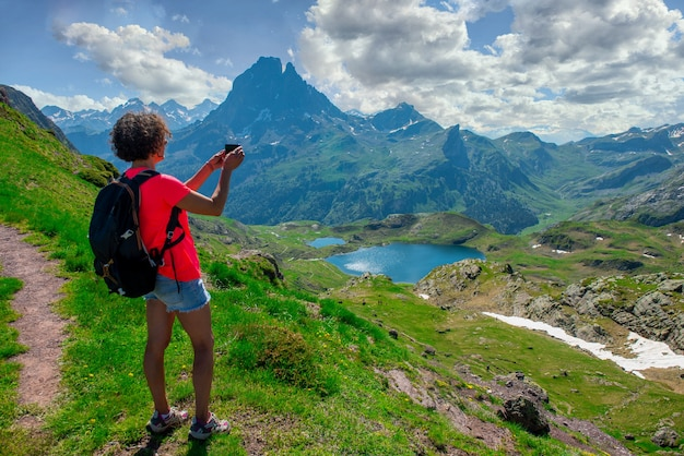 Hiking woman taking a picture of pic du midi ossau in the french pyrenees mountains