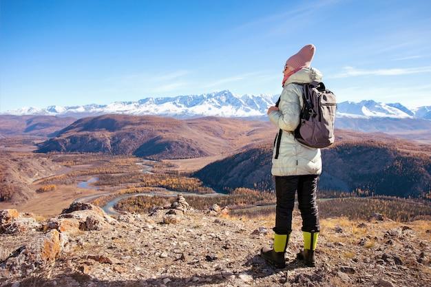 Пешие прогулки женщина с рюкзаком, глядя на вдохновляющие осенние горы.