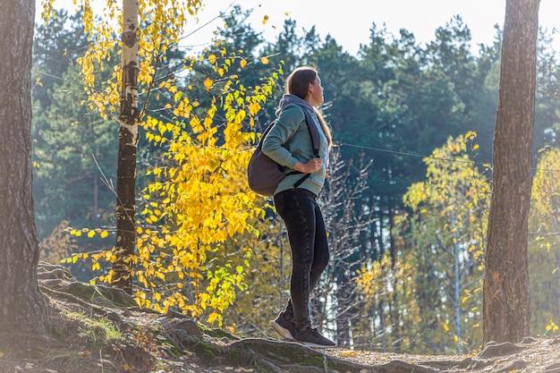 山の上に立っているバックパックとハイキングの女性