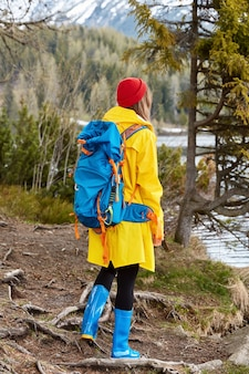 Hiking woman with rucksack stands by lake, enjoys view in nature, wears yellow raincoat and rubber boots