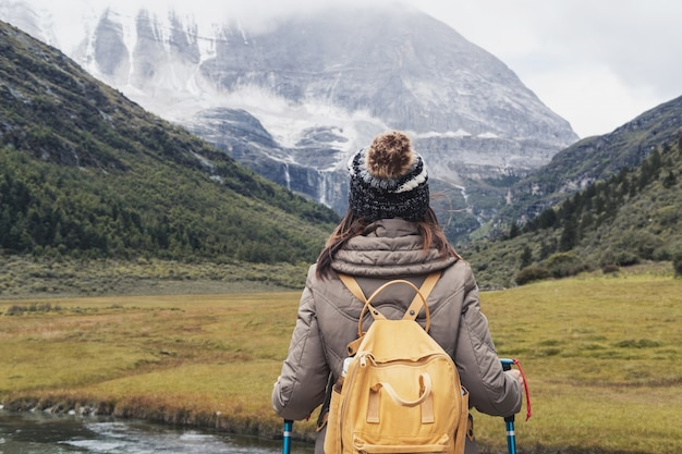 Hiking young woman traveler with backpack looking beautiful landscape