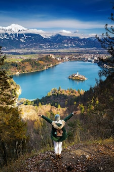アルプス山脈と高山湖を背景にハイキング若い女性。旅行スロベニア、ヨーロッパ。背景に城と山々があるブレッド湖のカトリック教会と島の平面図。