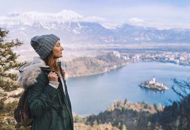 背景にアルプス山脈と高山湖と若い女性をハイキング旅行スロベニアヨーロッパ