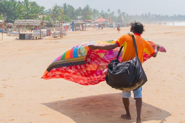 Hikkaduwa, sri lanka. the seller covered the demonstrates his goods.