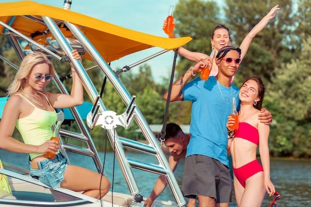 재미있는 축하. 맑은 여름날 유람선에서 자유 시간을 보내는 행복한 현대 젊은이들의 회사