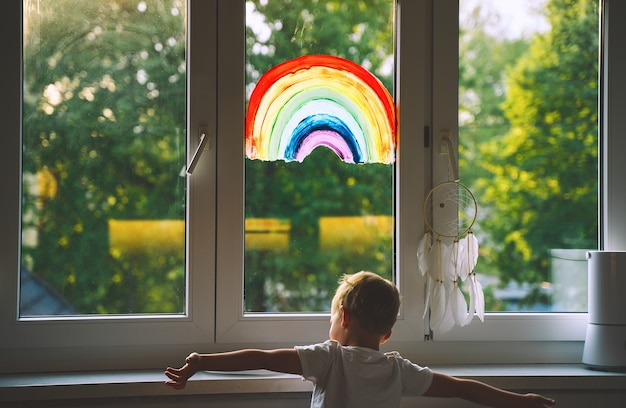 Ãâã'â¡hild boy on background of painting rainbow on window. photo of kids leisure at home. positive visual support during quarantine pandemic coronavirus covid-19 at home. family art background