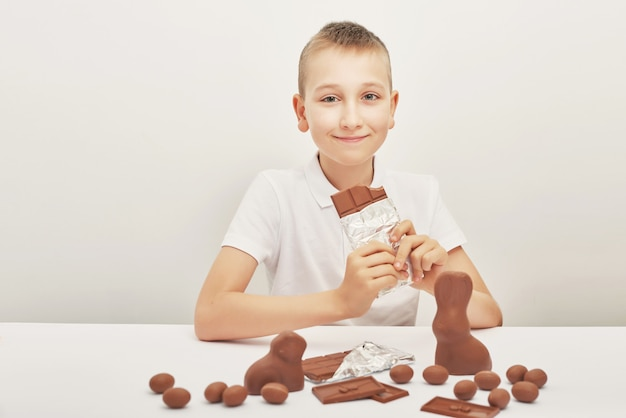 Ð¡hild boy with chocolate bunnies and eggs for easter. chocolate eggs, rabbits and tiles. chocolate sweets for children