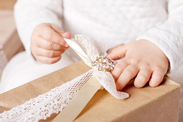 ギフトボックスを持っているhildの手。クリスマス、ヒューイヤー、誕生日のコンセプト。ボケ味と日光とお祭りの背景。魔法のおとぎ話