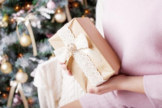 Руки ребенка держат подарочную коробку. рождество, год, день рождения. праздничный фон с боке и солнечным светом. волшебная сказка