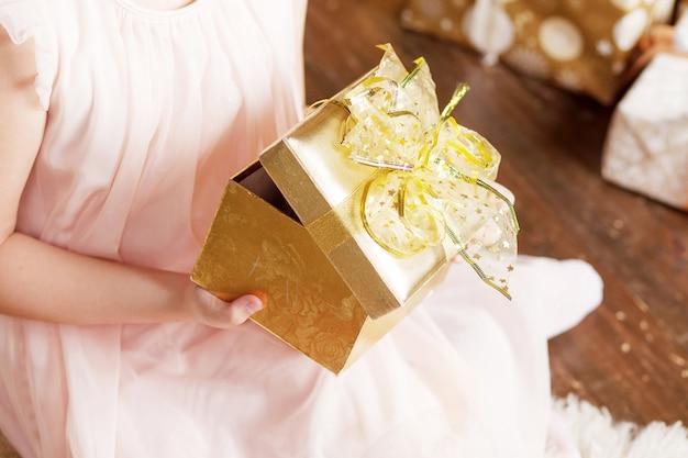 Руки ребенка держат золотую подарочную коробку. рождество, год, день рождения.