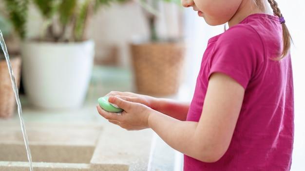 Хильда моет руки с мылом в домашних условиях. концепция защиты от вирусов.