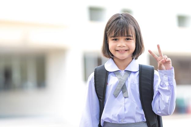 学校に戻ってカメラを見ている制服とバックパックのhildren学生