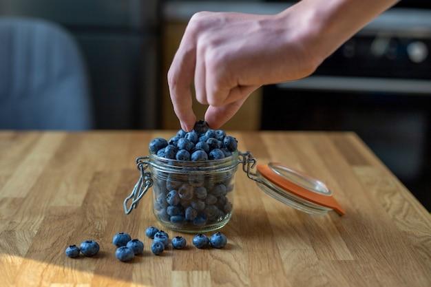 Детская рука берет чернику из стеклянной банки на кухонном столе здоровый завтрак
