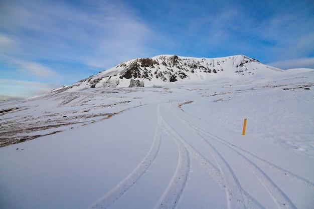 アイスランドの冬の間、日光と青い空の下で雪に覆われた丘