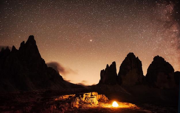 Ночью холмы запечатлены разноцветными звездами и млечным путем. туристы в палатке. горы тре чиме с тремя вершинами.