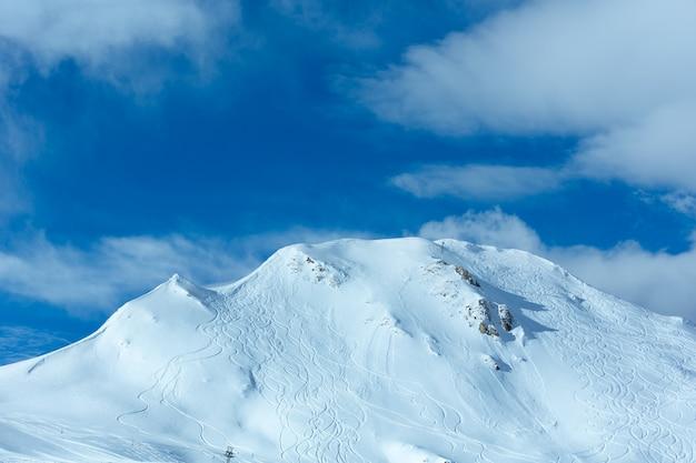 언덕은 푸른 하늘에 스키 트랙과 구름을 기복합니다. 겨울 오스트리아.