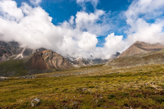 Склон холма с высокими вершинами в облаках. скалы с реками из камней. голубое небо. зеленая трава на склоне. много камней. по горизонтали.