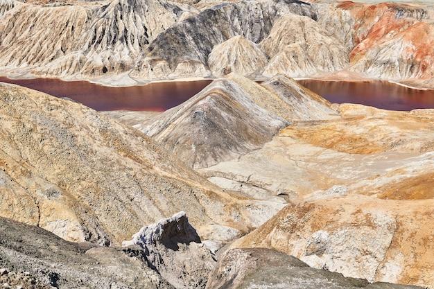 Холмистая пустыня с красным озером на дне оврага на месте старого глиняного карьера
