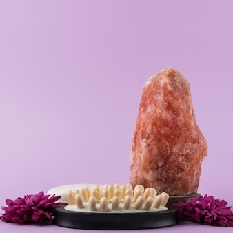 Himalayan pink rock salt; massage brush and flower against purple background