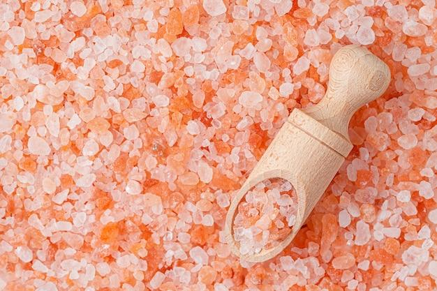 ヒマラヤピンクの塩の背景と木製のスクープ。真上。