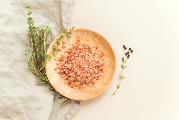ヒマラヤピンクの塩顆粒木製皿とタイムトセマリーとコショウフードスパイスフラットレイ