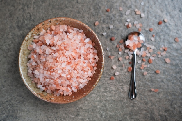 Гималайская розовая соль в миске на столе. вид сверху розовая соль с копией пространства.
